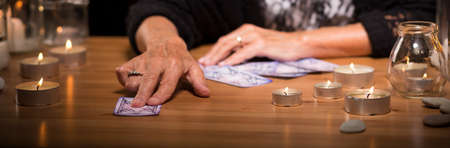 spirit medium: Old fortune teller is giving a card to her client Stock Photo