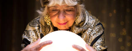 spiritualist: Fortune teller is seeing a future in a crystal ball