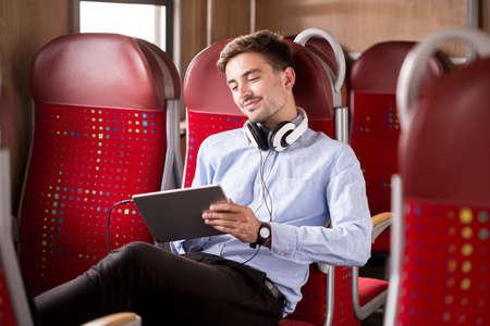 Foto de viajero moderno relajante en el tren después del trabajo Foto de archivo