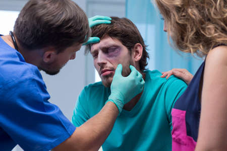 Beaten man with black eye in emergency room Stock Photo