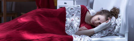 sleepless: Panorama of woman lying in bed sleepless because of pain Stock Photo