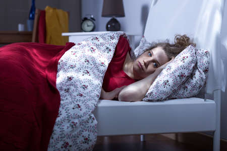 poor: Horizontal image of a young sleepless woman lying in bed