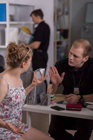 interrogating: Police officer interrogating young woman at police station Stock Photo