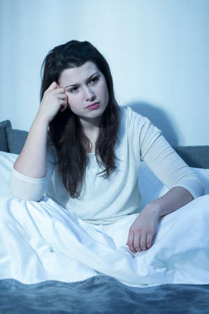 restless: Young pretty girl with insomnia sitting at night Stock Photo