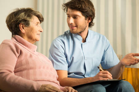 health elderly: Image of senior female talking with doctor during home visit