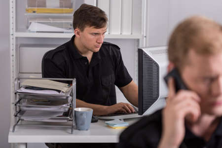police officer: Policeman sitting at the desk and using computer at work