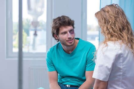 Bruised man flirting with nurse in treatment room