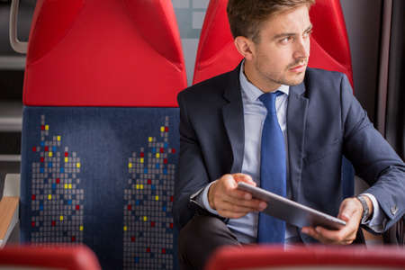 young businessman: Picture of businessman in suit using public transport