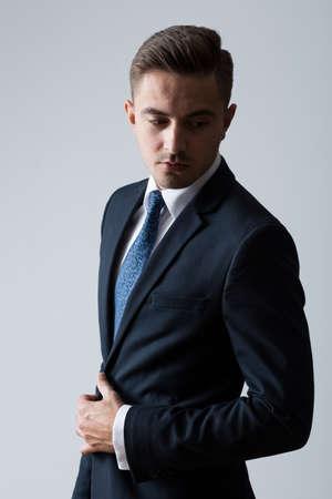 hombres jovenes: Hombre de moda joven posando sobre fondo brillante Foto de archivo