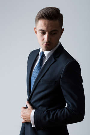 men in suit: Young fashionable man posing on bright background