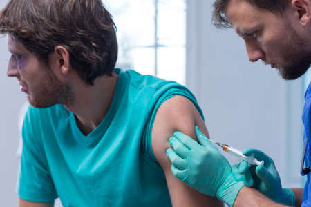 injection: Doctor doing injured man tetanus toxoid injection