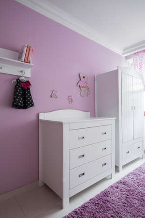 baby wardrobe: White furniture and rose wall in babys room