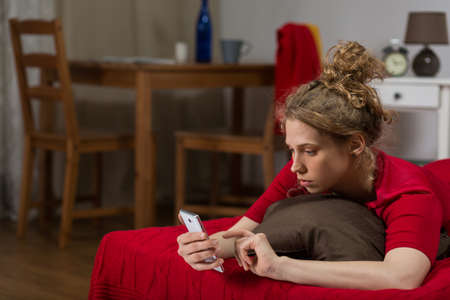 dullness: Horizontal photo of a lonely and bored girl using smartphone