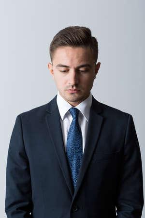 hombres jovenes: Hombre de negocios pensativo joven de moda mirando hacia abajo