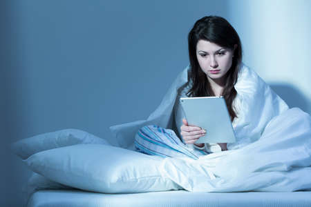 tired person: Tired woman in bed reading book online at night