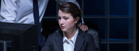after hours: Young woman has to stay after hours in the office