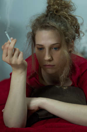 friendless: Photo of a young miserable woman smoking cigarette in bed Stock Photo