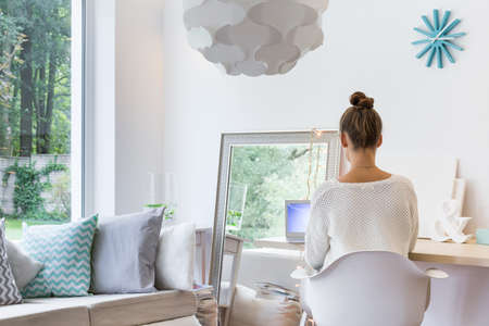 mirror image: Image of woman sitting on chair in cozy interior
