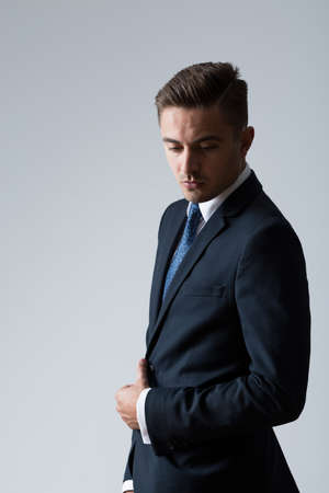 forceful: Studio shot of elegant young man in navy suit