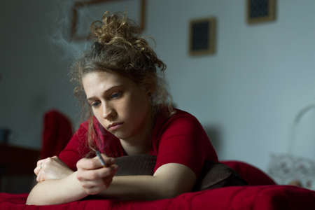 woman in bed: Panorama of young woman in bed feeling secluded and miserable Stock Photo
