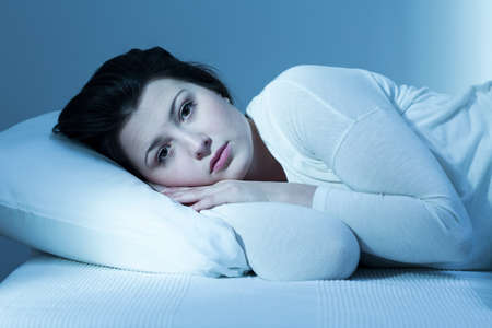 Troubled young woman in bed and lack of sleep Stock Photo