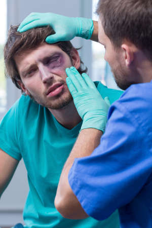 diagnosing: Doctor diagnosing young man with eye bruise