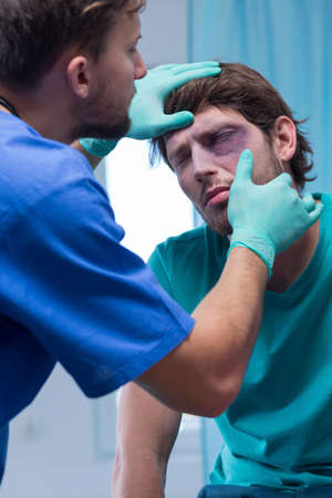 diagnosing: Male doctor diagnosing injured man with shiner