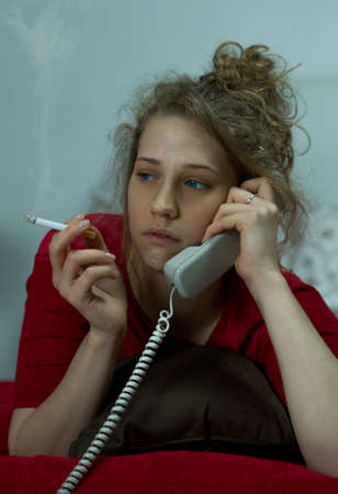 phoning: Image of a teraful woman smoking cigarette and phoning friend