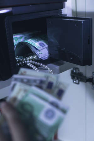 safe house: Photo of domestic safe with money and pearl necklace Stock Photo