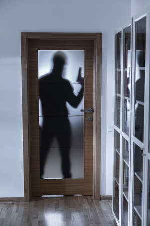 burglar: Photo of shadow of burglar with gun behind doors Stock Photo