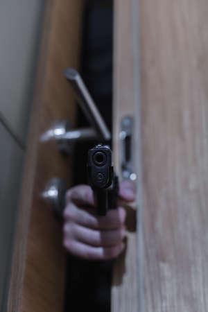 pointing gun: Photo of armed robber behind doors pointing gun Stock Photo