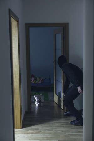 pedophilia: Photo of pedophile in black walking into child room