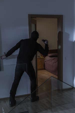 intruder: Image of masked dangerous intruder in house