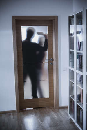 intruder: Shadow of dangerous intruder attacking innocent person Stock Photo