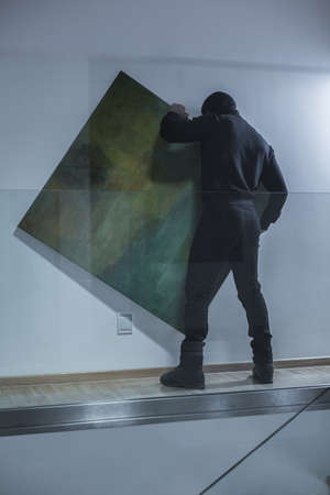 Picture of man in black stealing piece of art
