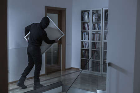 robbing: Image of robber in black mask stealing picture Stock Photo