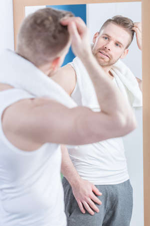 narcissistic: Man looking in the mirror is pleased with his reflection