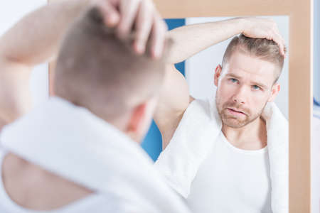 worrying: Man is worrying about wrinkle on his forehead