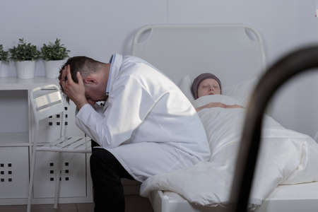 patient in hospital: Picture of a sad doctor grieving his patient Stock Photo