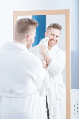 narcissistic: Young man drying his face with a towel