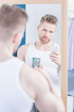 narcissistic: Handsome guy is taking photo of himself in the mirror