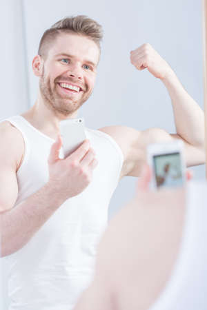 narcissistic: Young masculine man is stretching his bicep to selfie Stock Photo