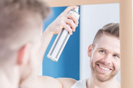 narcissistic: Man is styling his hair using hairspray Stock Photo