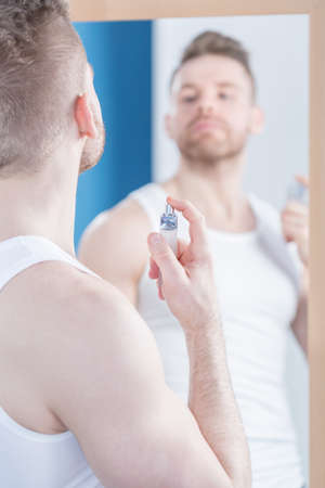 narcissistic: Handsome good looking man is applying perfume