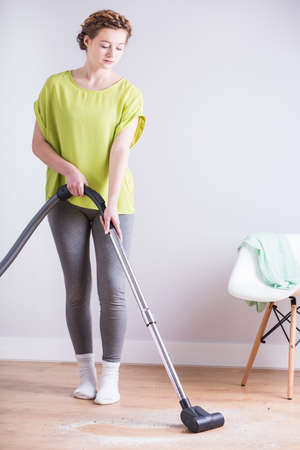 dirty room: Young busy woman vacuuming her dirty room Stock Photo