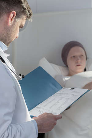 finding a cure: Concerned doctor is reading his patients charter Stock Photo