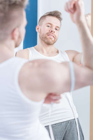 girth: Young muscular man is measuring how big is his bicep
