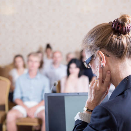 lecturer: Image of female lecturer during presentation for group of businesspeople Stock Photo