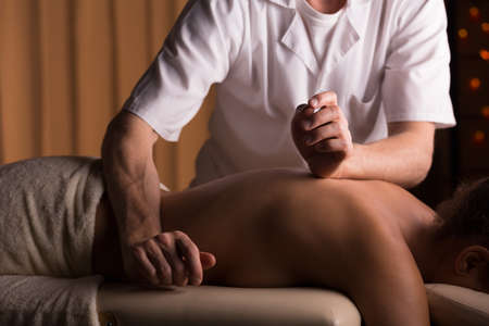 spinal manipulation: Experienced physiotherapist doing womans spinal column manipulation