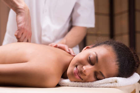 mobilization: Young happy woman in spa having spine mobilization